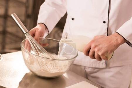 partial view of confectioner adding milk into dough in restaurant kitchen