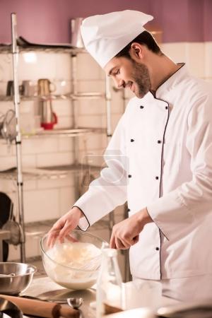 cheerful confectioner in chef hat making dough in restaurant kitchen