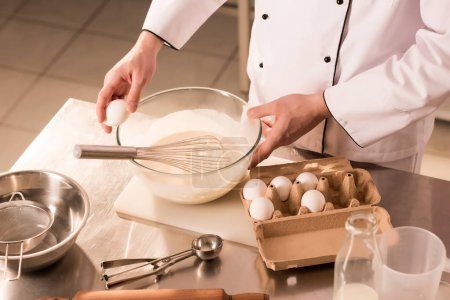 Photo for Partial view of confectioner adding raw egg into dough in restaurant kitchen - Royalty Free Image
