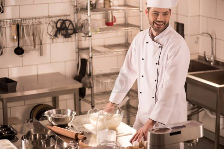 Photo for Cheerful confectioner standing at counter in restaurant kitchen - Royalty Free Image