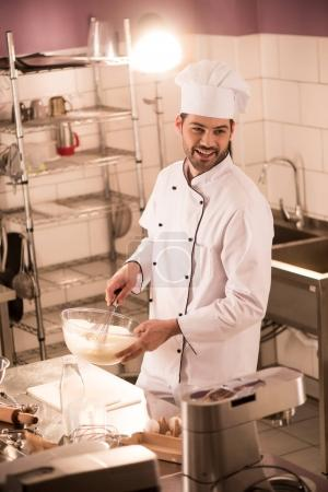 Photo for Smiling confectioner in chef hat making dough in restaurant kitchen - Royalty Free Image