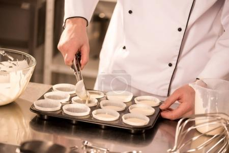 Photo for Cropped shot of confectioner pouring dough into baking forms - Royalty Free Image