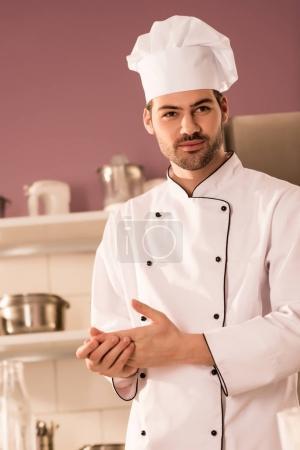 portrait of handsome confectioner in chef hat in restaurant kitchen