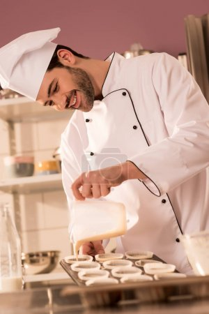 Photo for Smiling confectioner pouring dough into baking forms in restaurant kitchen - Royalty Free Image