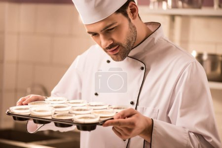 confectioner checking dough in baking forms in restaurant kitchen
