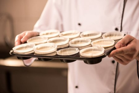 partial view of confectioner with baking forms full of raw dough in hands