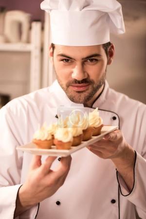 Photo pour Portrait de jeune confiseur regardant des cupcakes sur une assiette dans les mains - image libre de droit