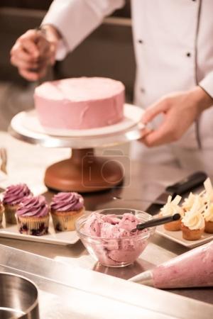 cropped shot of confectioner making cake in restaurant kitchen