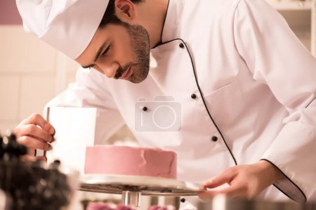 Photo for Focused confectioner making sweet cake in restaurant kitchen - Royalty Free Image