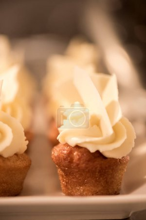 close up view of sweet cupcakes on plate on counter in restaurant kitchen