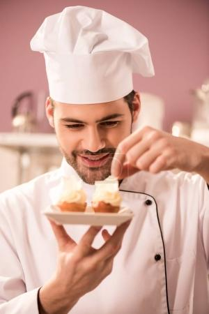 Photo for Portrait of smiling confectioner decorating cupcakes in restaurant kitchen - Royalty Free Image