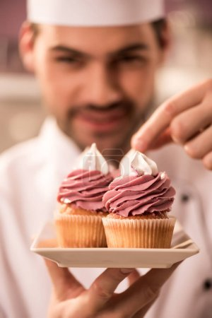 selective focus of confectioner decorating cupcakes in restaurant kitchen