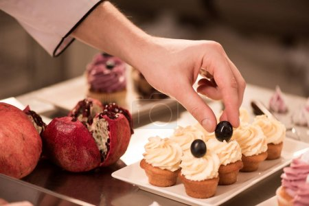 Photo for Cropped shot of confectioner decorating sweet cupcakes - Royalty Free Image
