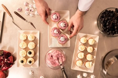 Photo for Top view of confectioner arranging cupcakes on plate - Royalty Free Image