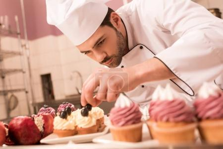 Photo for Confectioner decorating cupcakes in restaurant kitchen - Royalty Free Image