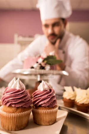 selective focus of cupcakes and confectioner standing near cake on counter in restaurant kitchen