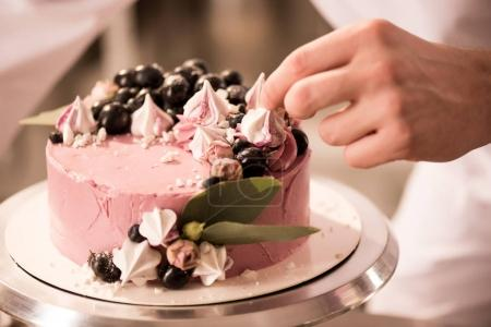 partial view of confectioner decorating sweet cake
