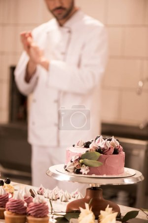 selective focus of cake, cupcakes and confectioner in restaurant kitchen