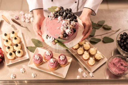 Photo for Partial view of confectioner holding cake in hands in restaurant kitchen - Royalty Free Image