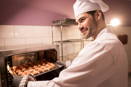 smiling confectioner holding eclairs on baking pan in hands