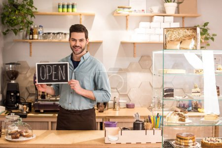 Photo for Smiling barista with open blackboard in hands at counter in coffee shop - Royalty Free Image