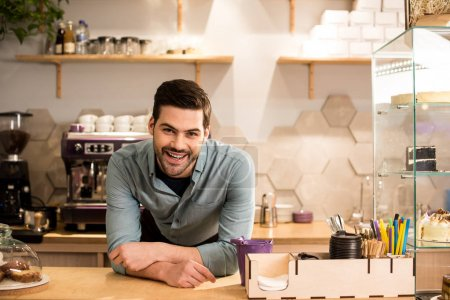 portrait of cheerful barista leaning on counter in coffee shop