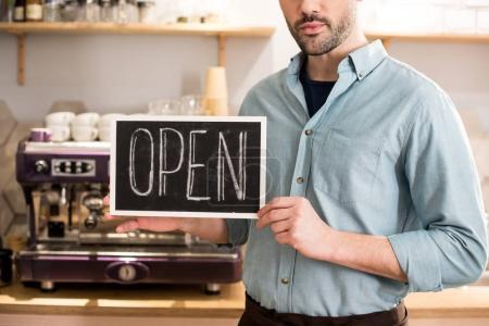 Photo pour Vue partielle de barista avec tableau ouvert dans les mains dans le café - image libre de droit