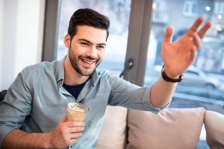 portrait of smiling man with ice coffee waving to someone in cafe
