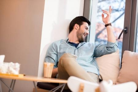 Photo for Cheerful man looking out window in coffee shop - Royalty Free Image