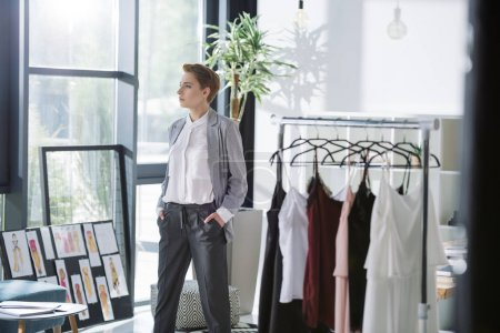 stylish fashion designer at modern office with lot of dresses on hangers