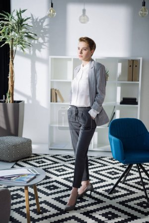 fashionable young businesswoman standing at modern office and looking away