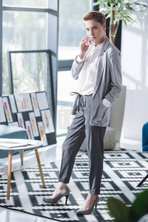 attractive young fashion designer talking by phone at office