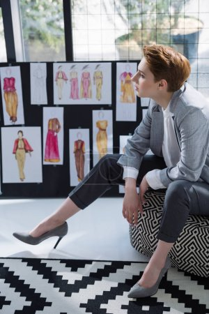 young fashion designer sitting at office in front of board with various sketches