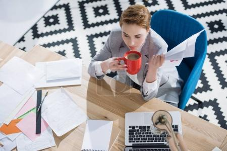 high angle view of young businesswoman drinking coffee while doing paperwork