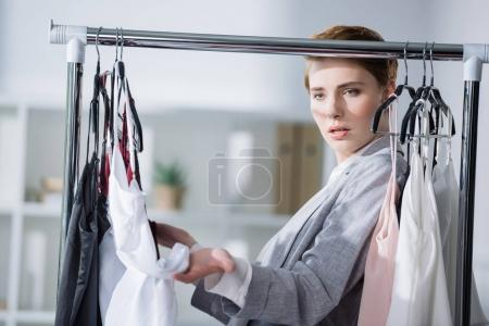 fashion designer examining quality of clothing on rack
