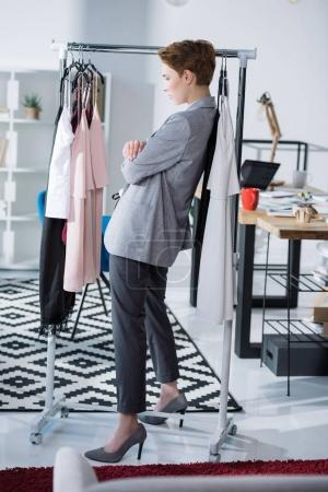 serious fashion designer standing under rack with clothing