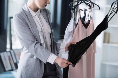 Photo pour Recadrée tir de qualité examen de styliste de vêtements sur la grille - image libre de droit