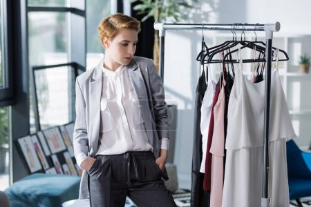 young fashion designer looking at clothing on rack