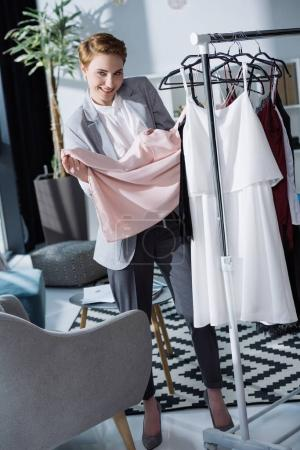 happy young fashion designer examining quality of clothing on rack