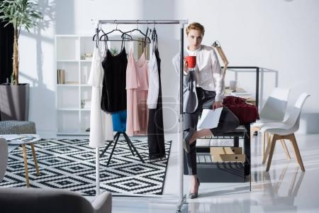 young stylish fashion designer sitting on desk at office