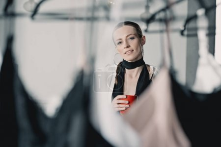 stylish young woman with coffee mug looking at clothes on rack