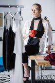 young attractive fashion designer sitting on work desk with cup of coffee and looking at dresses