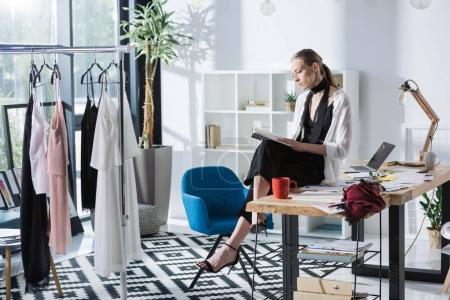attractive young fashion designer sitting on work desk and reading