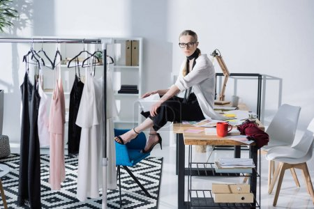 attractive young fashion designer sitting on work desk