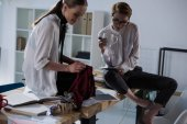 stylish young fashion designers sitting on table and working together at clothing design studio