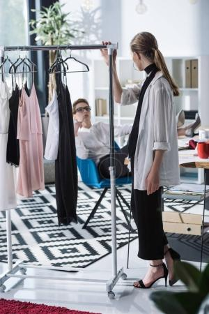 young fashion designers discussing new dresses on rack