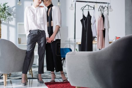 Photo pour Couturiers couple lesbien tenant la main au bureau - image libre de droit