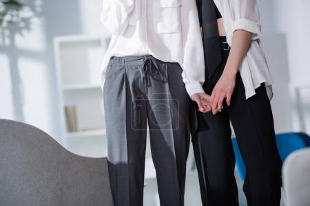 Photo pour Plan recadré de couple lesbien élégant tenant la main - image libre de droit
