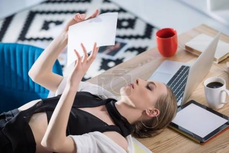 Photo for Attractive fashion designer lying on desk and looking at sketch - Royalty Free Image