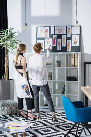 stylish young fashion designers looking at clothing sketches
